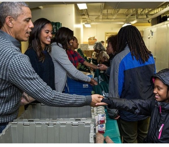 Barack Obama offers Thanksgiving message: pictured distributing food to people to celebrate it